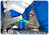 Several decontamination personnel wet sponges inside the unit in preparation for the arriving patients, while . . .